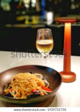 Blur picture background of spaghetti and white wine at local restaurant in Bangkok,  Thailand,  Asia.