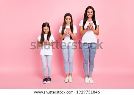 Full length body size photo mother daughters smiling using cellphones browsing internet isolated pastel pink color background