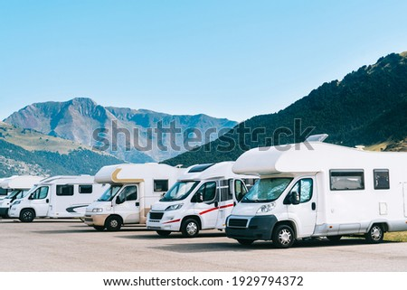 Summer tourism with RV in the mountain. Campers parked in a row in a caravan parking area. Best option for travel. Motorhomes and campingcar. Royalty-Free Stock Photo #1929794372