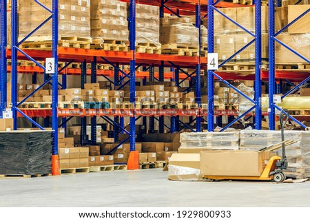 Interior of a modern warehouse storage of retail shop with pallet truck near shelves Royalty-Free Stock Photo #1929800933