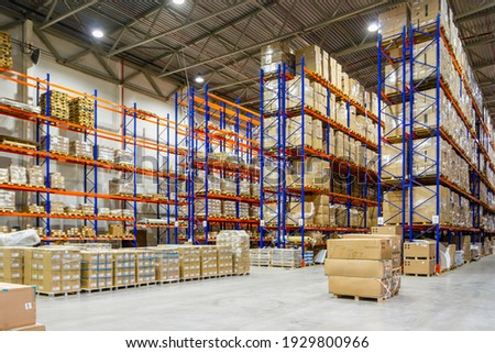 Interior of a modern warehouse storage of retail shop with pallet truck near shelves Royalty-Free Stock Photo #1929800966