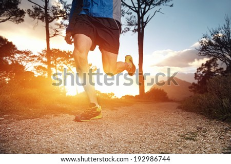 trail runner man exercising for fitness at sunrise in mountains doing sport #192986744