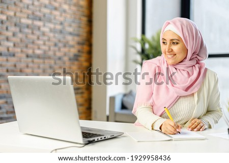 Smiling muslim businesswoman taking notes sitting at the desk in modern office space. Young islamic female student wearing hijab and smart casual wear overwrites from the laptop screen into notebook Royalty-Free Stock Photo #1929958436