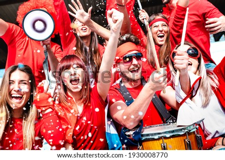 Football supporter fans cheering with confetti watching soccer match at stadium tribune - Young people group with red t-shirt having excited fun on sport championship - Bright vivid filter Royalty-Free Stock Photo #1930008770