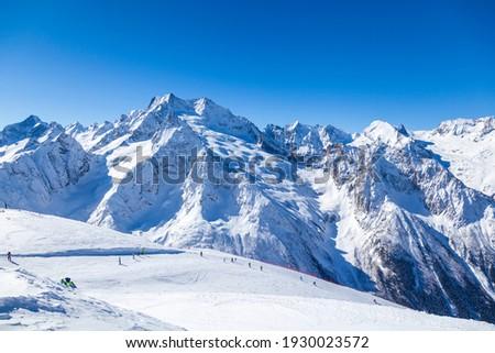 Caucasus Mountains, Panoramic view of the ski slope with the mountains Belalakaya, Sofrudzhu and Sulakhat on the horizon in winter day. Dombai ski resort, Western Caucasus, Karachai-Cherkess, Russia. Royalty-Free Stock Photo #1930023572