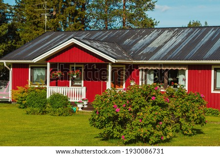 beautiful red house and big bushes of flowers , beautiful pictures