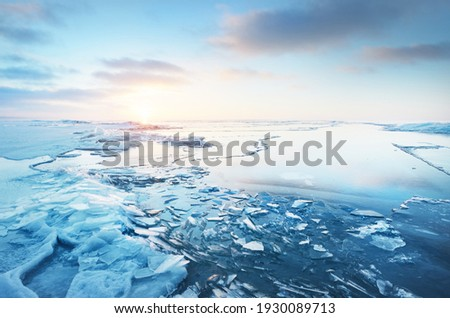 Panoramic view of the snow-covered shore of the frozen Baltic sea at sunset. Ice fragments close-up. Colorful cloudscape, soft sunlight. Symmetry reflections on the water. Christmas, seasons, winter Royalty-Free Stock Photo #1930089713