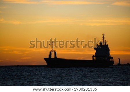 a silhouette of a cargo ship at sunset. Royalty-Free Stock Photo #1930281335