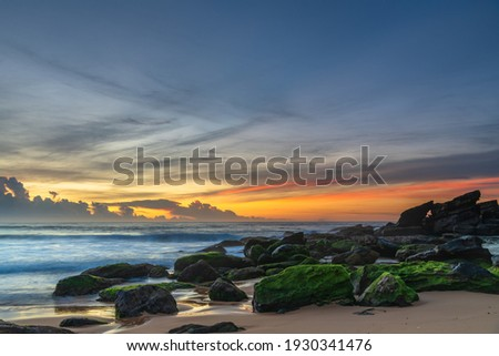 High clouds drift over a cloud bank on the horizon, a sunrise seascape from Killcare Beach on the Central Coast, NSW, Australia. Royalty-Free Stock Photo #1930341476
