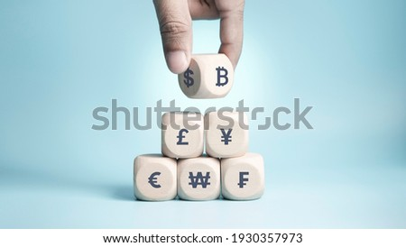 Bitcoin Concept, Bitcoin transfer, Hand of business man choose and turn dollar to bitcoin, wood cube stacking with currency icon on blue background, photo for investment bitcoin content
