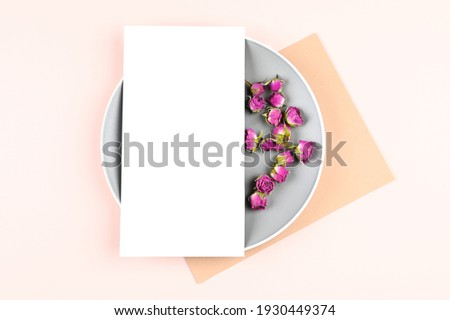 Vertical blank white card on circle stand and pastel paper, dried rose buds on background. Empty space. Styled stock photo, web banner. Flat lay, top view. High quality photo
