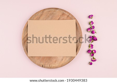 Horizontal blank brown card on circle background and pastel paper, dried rose buds on background. Empty space. Styled stock photo, web banner. Flat lay, top view. High quality photo