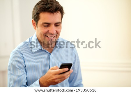 Portrait handsome businessman texting with his cellphone while smiling on closeup background - copyspace #193050518
