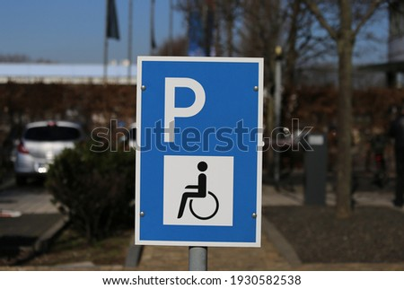 Closeup of isolated blue white reserved for disabled people parking space sign, blurred background