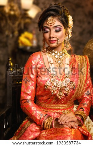 Magnificent young Indian bride in luxurious bridal costume with makeup and heavy jewellery is sitting in a chair in with classic vintage interior in studio lighting. Wedding fashion. Royalty-Free Stock Photo #1930587734