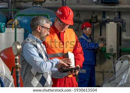 Technical Manager Using Digital Tablet and Discussing About Production Process with Power Plant Worker. District Heating Power Plant. Digital Technology and Teamwork Concept. Industry 4.0  Royalty-Free Stock Photo #1930613504