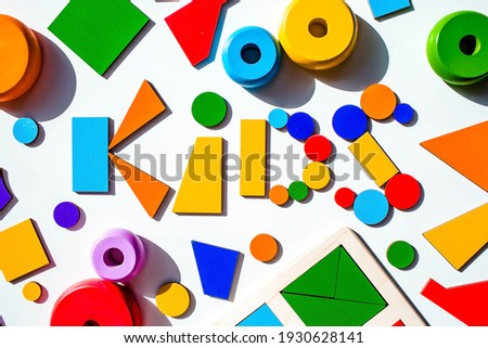 Word kids made of wooden toys on a white isolated background. Children's educational logic toys used in Montessori Games for development.