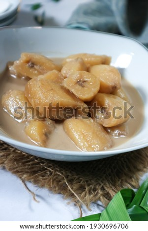 Unfocus picture of bowl of Kolak pisang, Indonesian dessert, made from kepok banana cooked with palm sugar, coconut milk, pandanus leaves on white background. Very popular during Ramadhan. Isolated