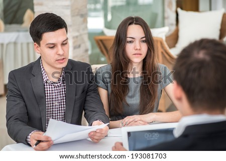 Three young businessman sitting at the table and discussing business affairs.Successful businessmen discussing business on a tablet.Couple man and woman sitting at the table and smiling to each other #193081703