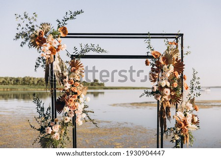 Wedding ceremony. On a green meadow on the seashore there is an arch decorated with flower arrangements, chairs for guests, candles and lamps Royalty-Free Stock Photo #1930904447
