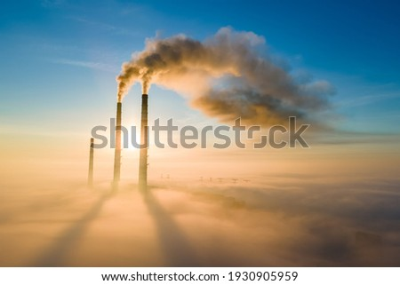 Aerial view of coal power plant high pipes with black smoke moving up polluting atmosphere at sunset. Royalty-Free Stock Photo #1930905959