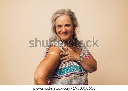 Senior woman looking happy after getting vaccine. Elderly female showing her arm with a bandage after receiving vaccination. Royalty-Free Stock Photo #1930950518