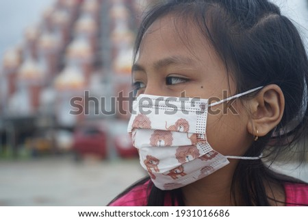 An Asian girl is sitting while wearing a unique mask