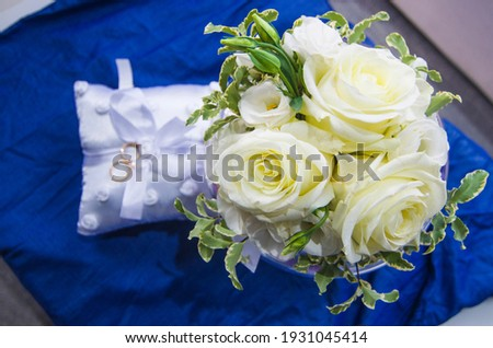 wedding rings on a white and soft pillow with beautiful and fragrant flowers, a symbol of love forever