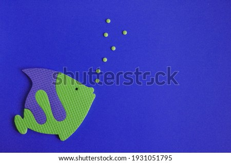 cartoon green and violet fish swims in the dark blue water and blows bubbles. Childhood toy. Concept sea and holiday