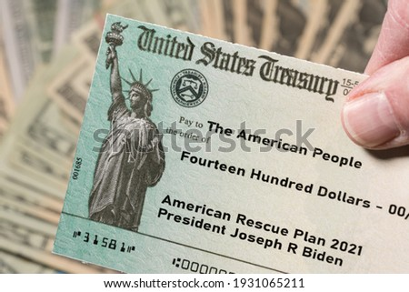 Stack of 20 dollar bills with US Treasury illustrative check to illustrate American Rescue Plan Act of 2021 payment on cash background Royalty-Free Stock Photo #1931065211