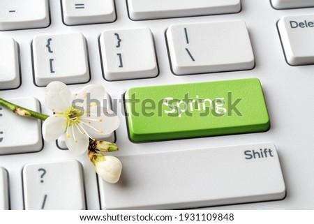 Green key with Spring word and cherry blossom with bud on a white computer keyboard. Spring season mood, holidays and sales concepts. Keypad enter button with message. Top view.  Royalty-Free Stock Photo #1931109848