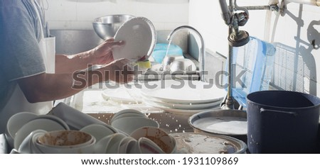 Man washing dish in sink at restaurant.People are washing the dishes too Cleaning solution Royalty-Free Stock Photo #1931109869