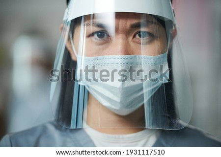 Young Asian serious nurse in uniform and protective workwear standing in front of camera and looking at you through transparent screen Royalty-Free Stock Photo #1931117510