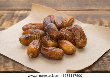 Dried dates on parchment paper close-up on the table. Dried fruits, healthy sweets, vegetarian food, fruits. Royalty-Free Stock Photo #1931117600