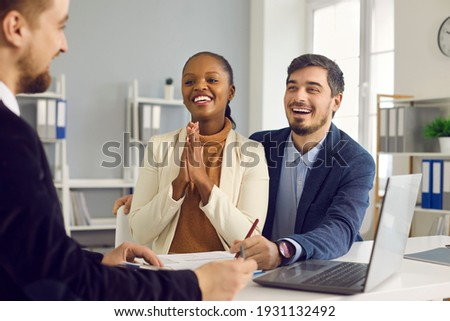 Happy young satisfied mixed ethnicity couple thanks bank manager broker. Grateful african amercian wife folding palm in pray gesture, happy smiling caucasian husband putting signature on paper Royalty-Free Stock Photo #1931132492