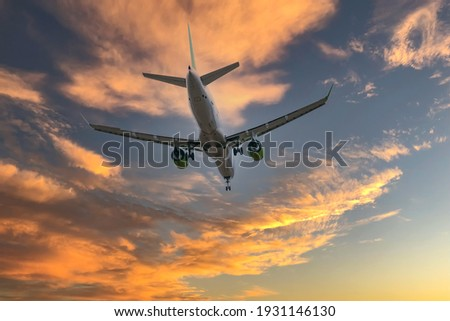 Airplane in the sky at sunrise or sunset Royalty-Free Stock Photo #1931146130