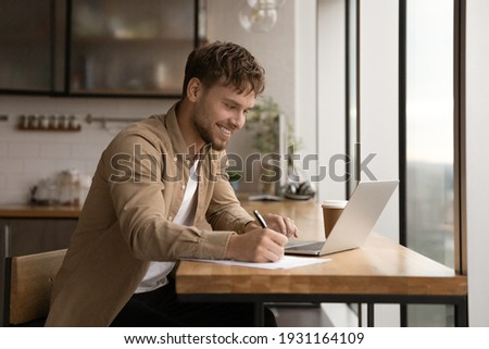 Close up smiling young man using laptop, writing, taking notes, watching webinar, training, involved in internet lesson, motivated positive student studying online at home, looking at laptop screen Royalty-Free Stock Photo #1931164109
