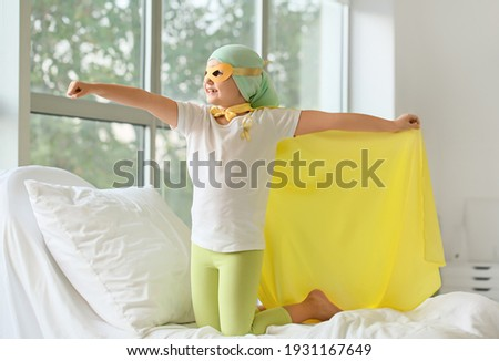 Little girl wearing superhero costume in clinic. Childhood cancer awareness concept Royalty-Free Stock Photo #1931167649