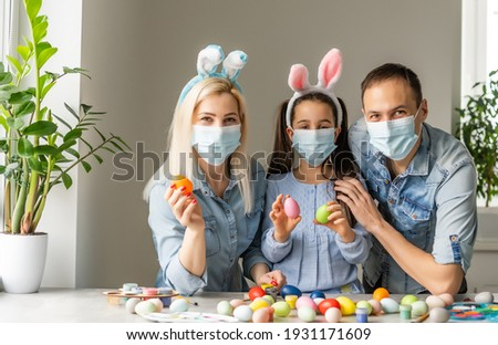 Dad, mom and child daughter at the table in medical masks are painting Easter eggs for the holiday. Happy easter family quarantined coronavirus. Happy at home.