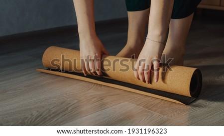 Woman unrolling cork yoga mat to practice yoga Royalty-Free Stock Photo #1931196323