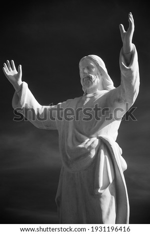 Close up shot from below of a statue of Jesus Christ, Christian icon, with arms open wide and a menacing attitude. Black and shite picture.