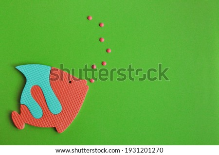 cartoon sky blue and red fish swims in the green water and blows bubbles. Childhood toy. Concept sea and holiday