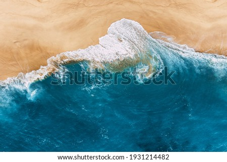 Blue ocean and clean sandy beach. Beautiful sea and wild beach with yellow sand. Blue ocean wave on a sandy beach. Top view of the tropical beach. Paradise island. Copy space Royalty-Free Stock Photo #1931214482
