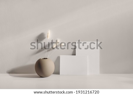 Modern summer stationery still life scene. Beige round vase with dry lagurus grass. Table background in sunlight. Blank business card, invitation mockups lean on champagne wall, long shadows.  Royalty-Free Stock Photo #1931216720