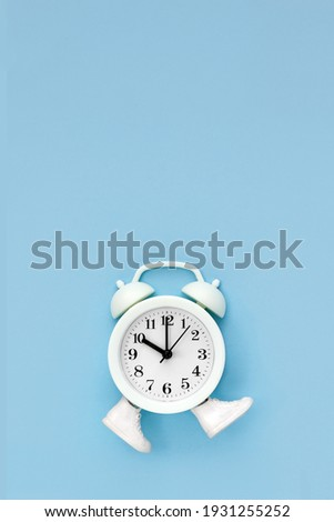 White alarm clock in toy sneakers walks on blue background. Time movement concept. Vertical poster, copy space