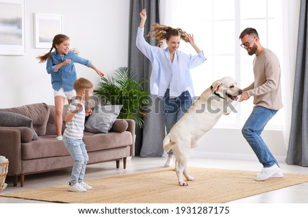 Full body of happy playful family: parents and little kids with cute purebred Labrador retriever dog having fun and dancing together in living room at home Royalty-Free Stock Photo #1931287175