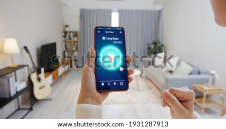 Asian young woman is using smart home app and touch screen to turn on the light by mobile phone Royalty-Free Stock Photo #1931287913