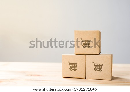 Online shopping ,Shopping cart logo on boxes on wooden table. Royalty-Free Stock Photo #1931291846