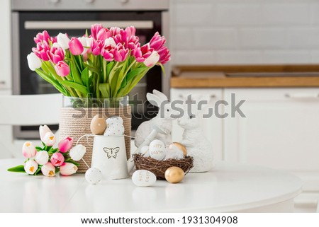 A bouquet of tulips, Easter bunnies and eggs with a golden pattern on the table. In the background is a white Scandinavian-style kitchen. Beautiful greeting card. The minimal concept. Royalty-Free Stock Photo #1931304908