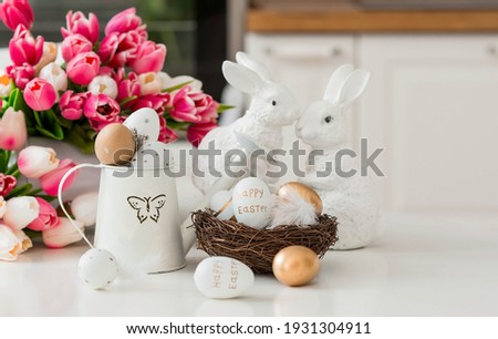 A bouquet of tulips, Easter bunnies and eggs with a golden pattern on the table. In the background is a white Scandinavian-style kitchen. Beautiful greeting card. The minimal concept. Royalty-Free Stock Photo #1931304911